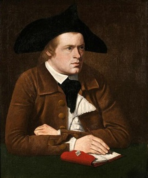 Young Man In Colonial Dress Seated At A Table With Notebook And Pen